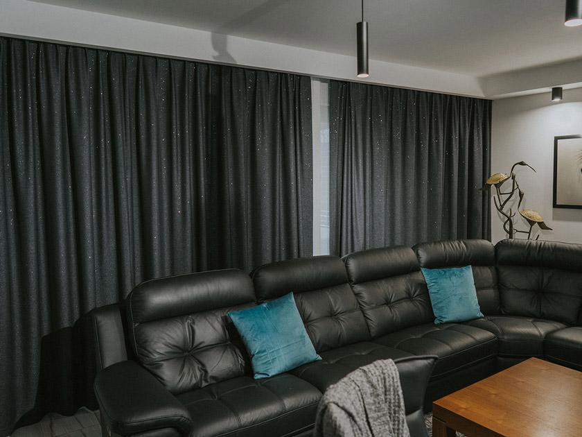 Skórzana kanapa, na niej turkusowe poduszki , czarne zasłony za którymi są panele japońskie