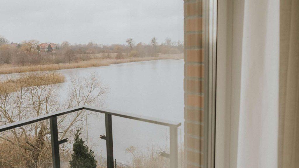 Okno balkonowe z widokiem na jezioro i lniane firanki