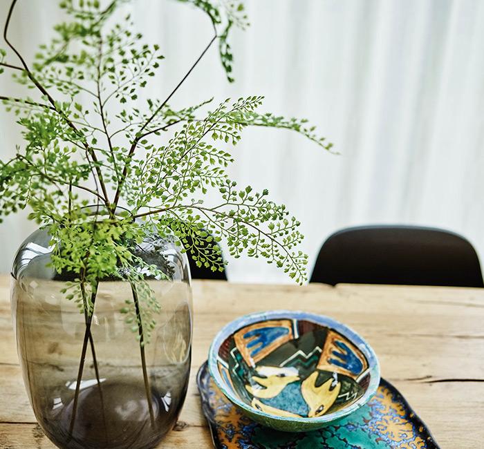 Zielona roślina na drewnianym stole w tle białe firany na wymiar