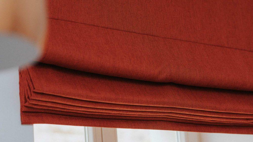 Czerwona, zaciemniająca roleta rzymska w sypialni