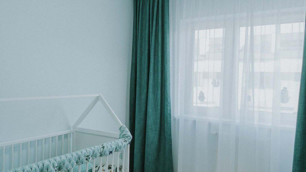 Białe, woalowe firany i turkusowe zasłony w pokoju dziecięcym