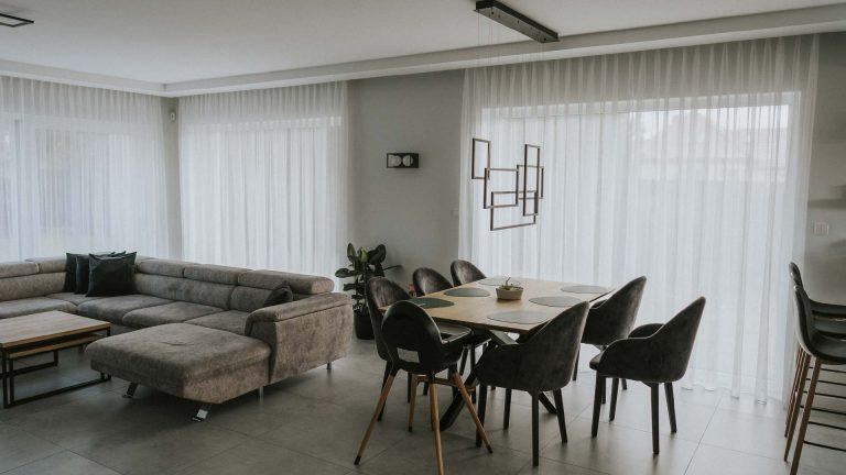 Woalowe firany na oknach tarasowych w salonie w stylu nowoczesnym