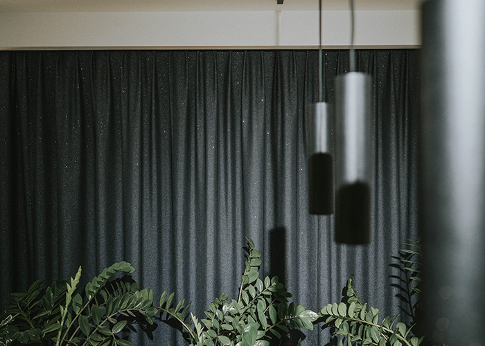 Srebrne lampy, rośliny i zasłony wiszące na karniszu elektrycznym