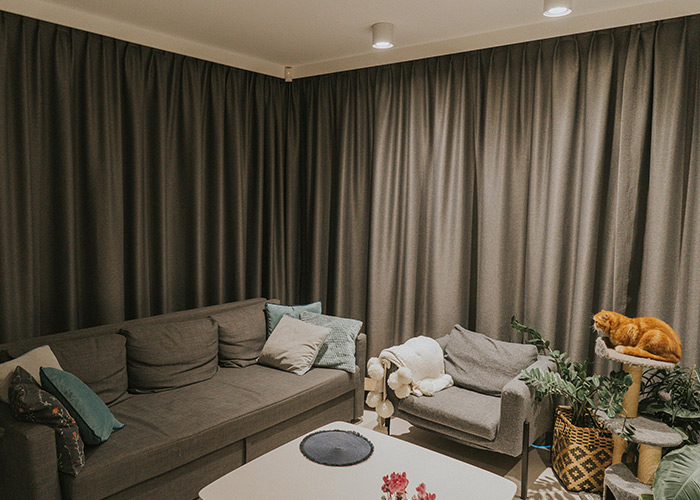 Szara, nowoczesna kanapa i poduszki, zasłony i karnisze elektryczne