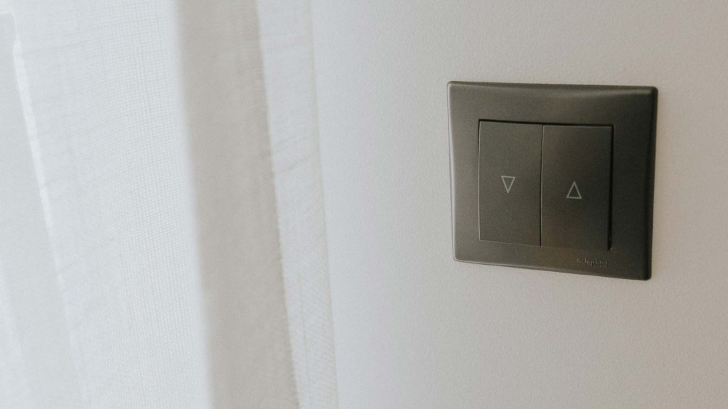 Czarny włącznik do karniszy elektrycznych na białej ścianie
