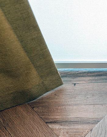 Kontrast rolety zwijanej i zasłony oraz drewnianej podłogi w domu w poznaniu