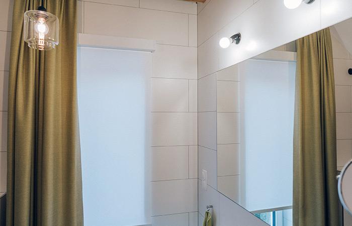 Roleta zwijana, karnisze elektryczny z zasłonami w jasnej lofotwej łazience