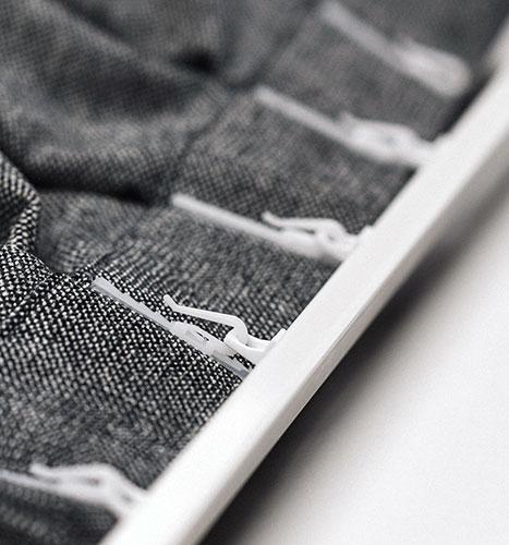 Zasłony z szarej tkaniny naturalnej zaczepione o ślizgi szyny ks