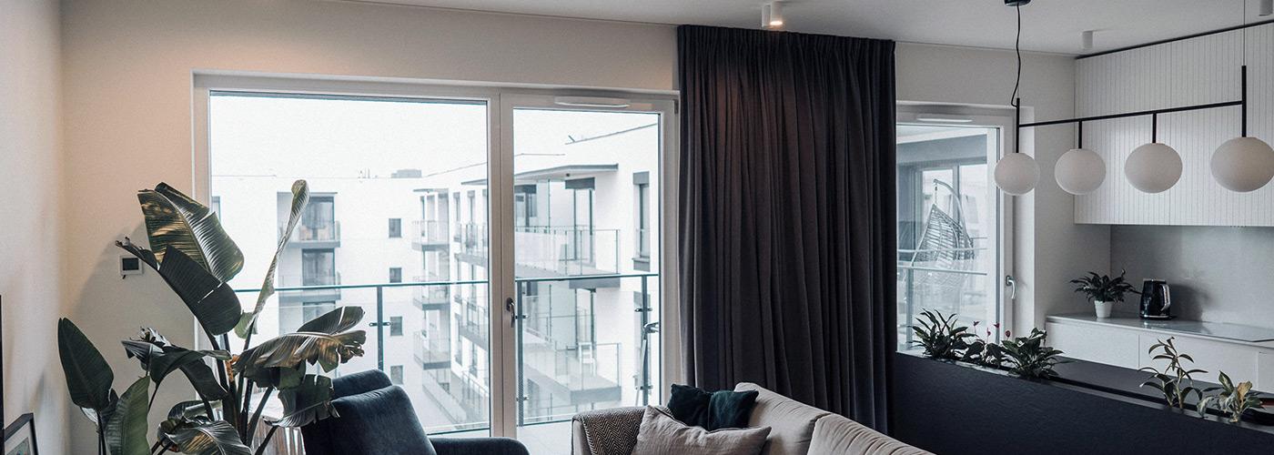 Welurowe, ciemno-szare zasłony na oknie balkonowym salonie z aneksem kuchennym