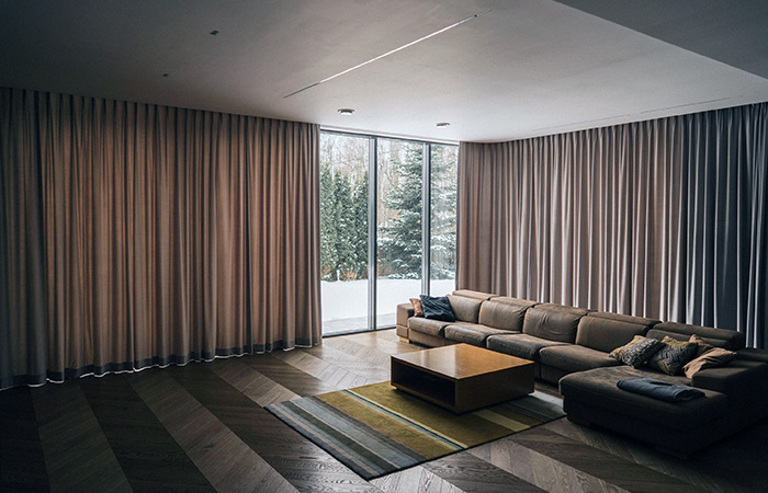 Zasłony na karniszach elektrycznych dekorujące okno tarasowe w nowoczesnym salonie