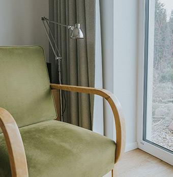 Drewniany fotel z zieloną tapicerką i naturalnie wyglądające zasłony w nowoczesnej stodole w poznaniu