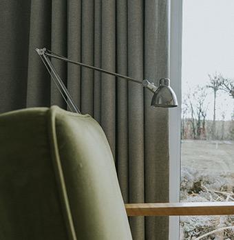 Metalowa lampa, zielony fotel i pofalowane zasłony dekorujące okna domy w mieście Poznań