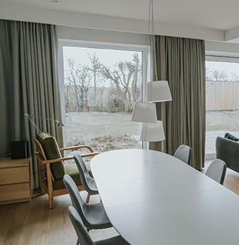 Biały stół, zielony, loftowy fotel i szare zasłony w salonie domu w mieście Poznań