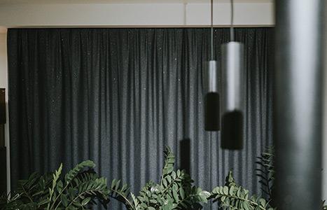 Srebrne lampy wiszące w kształcie walców, w tle zasłony z kryształkami