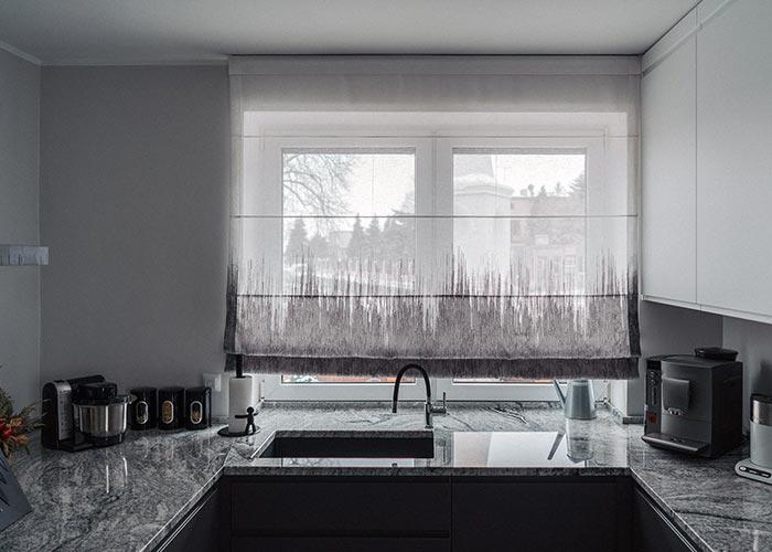 Biło-szara roleta rzymska z tkaniny o splocie naturalnym w kuchni