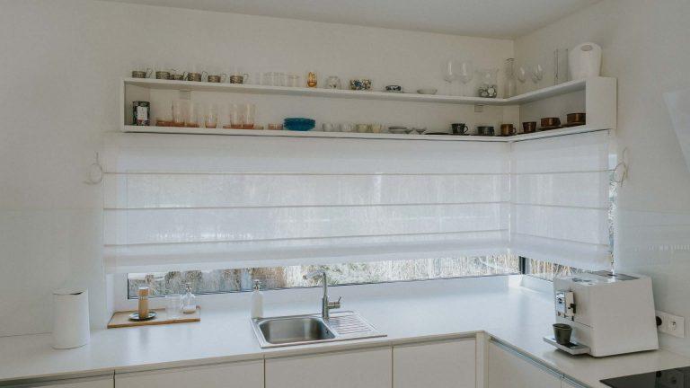 okno narożne w kuchni wyposażone w rolety rzymskie