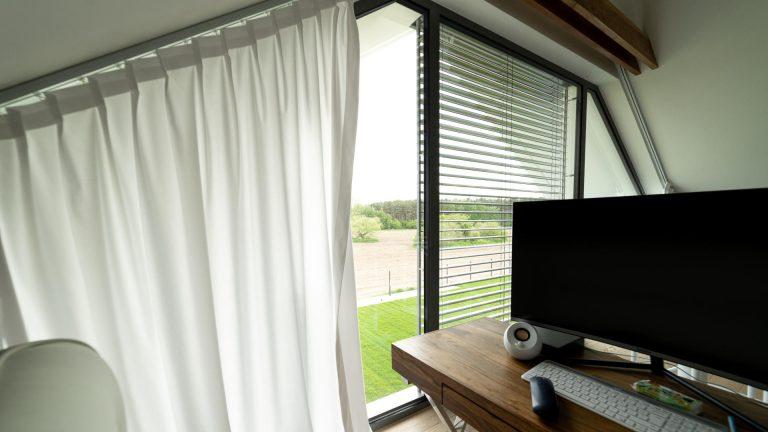 Białe zasłony i roleta wenecka na oknie trapezowym