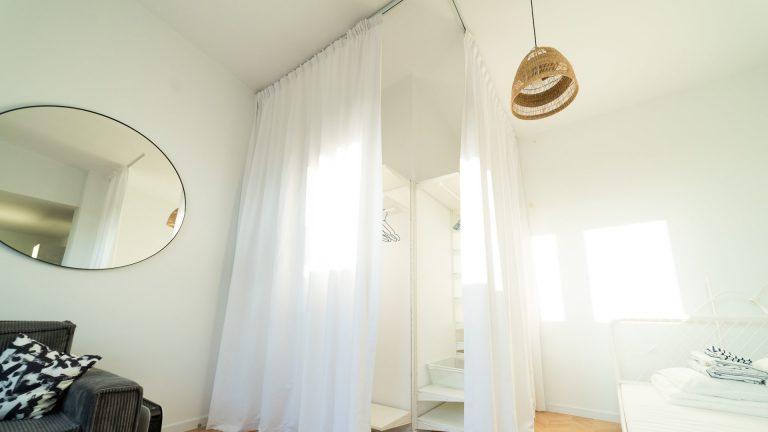 Białe zasłony zastępujące drzwi do szafo-garderoby