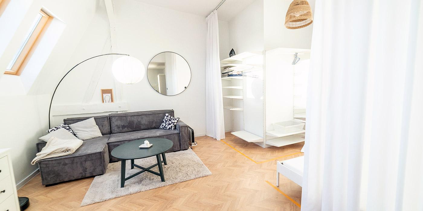 Przestronny salon w starej kamienicy i białe zasłony zastępujące drzwi do garderoby