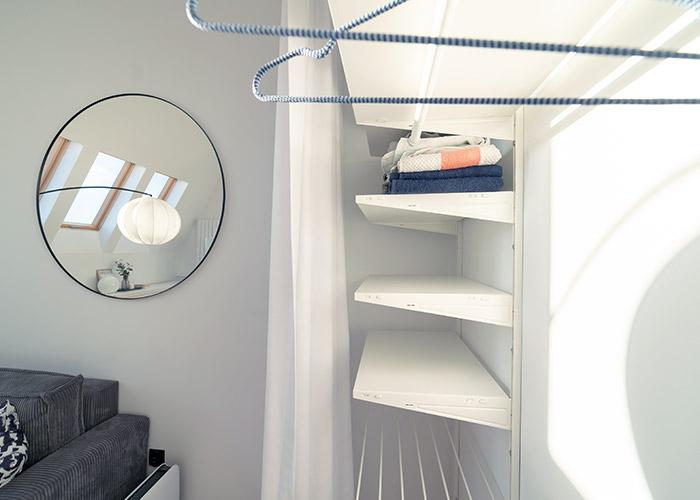 Metalowe półki za zasłonami w garderobie