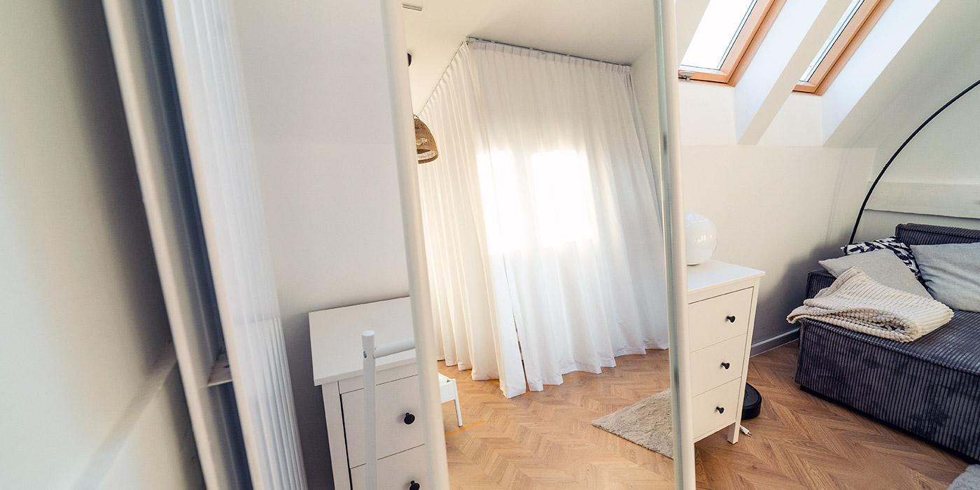 Zasłony zamiast drzwi do garderoby widoczne w odbiciu lustra
