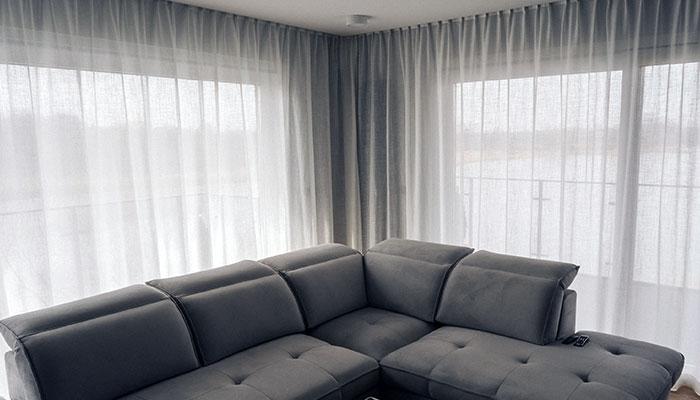 Narożne okno balkonowe zasłonięte białymi firankami