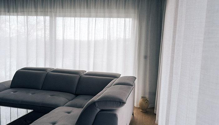 Lniane firanki na okno balkonowe i szara kanapa