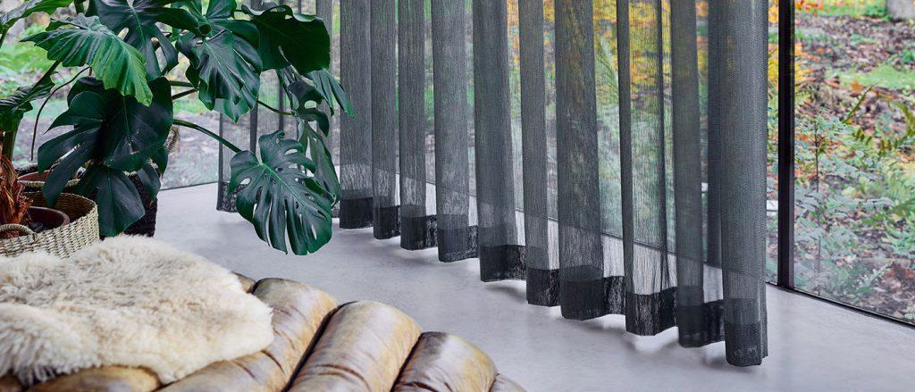 Szara firanka w połączeniu z betonową podłogą i rośliną