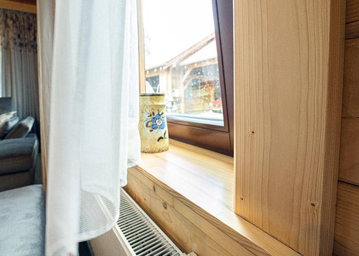 Firany oraz zasłony kaustyczne na drewnianych oknach wiejskiego domu