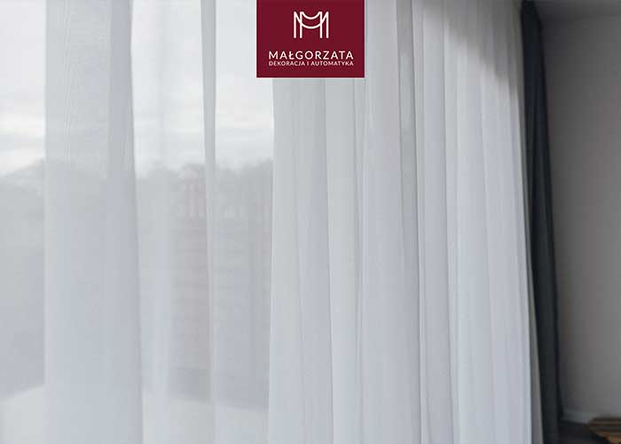 Białe woalowe firany na dużym okien tarasowym w salonie z bliska