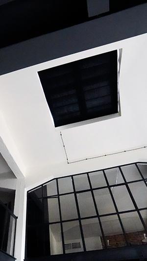 Elektryczna roleta do okna dachowego zasłaniająca świetlik w loftowym apartamencie
