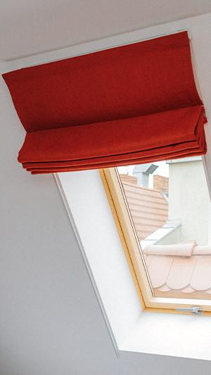 Czerwona roleta rzymska na okno dachowe w pokoju hotelowym