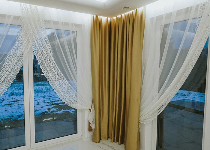 Narożne okno na ogród, złote zasłony i firany z haftowaniami