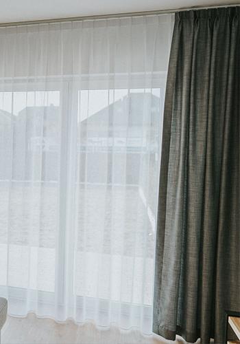 biała firanka okienna i szarawa zasłona
