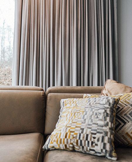 Welurowe zasłony, kanapa i kolorowe poduszki