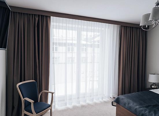 Firany i zasłony na haczykach w pokoju hotelowym